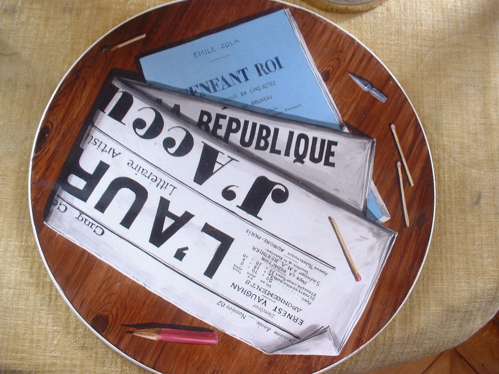 """Image - <em>J'Accuse </em>et <em>L'Enfant roi</em>"""" /></a></p> </div><h3>Commentaires</h3><p>Ce plat en trompe l'oeil est un hommage à Emile Zola, celui qui écrivit tout à la fois <em>J'Accuse </em>et le livret de <em>L'Enfant roi</em>, drame lyrique sur une musique d'Alfred Bruneau, représenté à l'Opéra-Comique en 1905.</p><h3>Auteur</h3><p>Non déterminé</p><h3>Date</h3><p>Vers 1905</p><h3>Origine</h3><p>Collection Puaux-Bruneau</p><h3>Mots-clés</h3><ul class="""