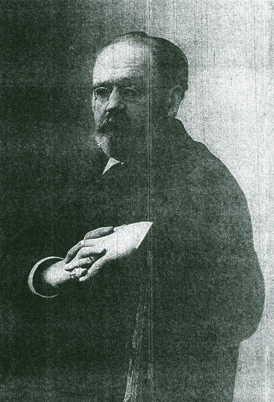 Image - Emile Zola assis, les mains croisées, le regard détourné