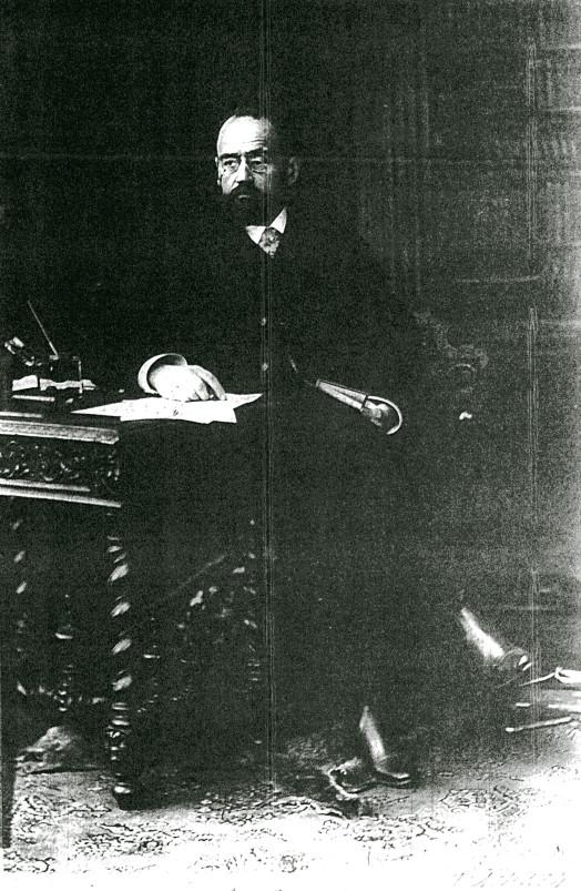 Image - Emile Zola derrière une table, un livre à la main